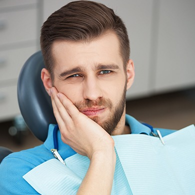 Man in dental chair holding jaw in pain